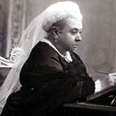 photo of Queen Victoria seated at desk, in thought, writing